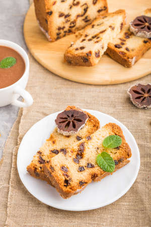 Homemade cake with raisins, dried persimmon and a cup of hot chocolate on a gray concrete background and linen textile. Side view, close up, selective focus.