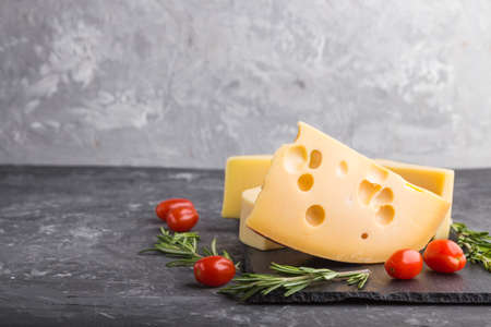 Various types of cheese with rosemary and tomatoes on black slate board on a black concrete background. Side view, close up, copy space, selective focus. 免版税图像