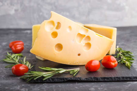 Various types of cheese with rosemary and tomatoes on black slate board on a black concrete background. Side view, close up, selective focus.