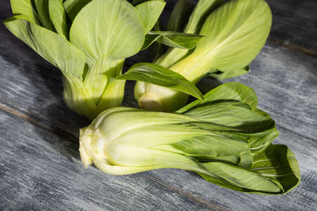 Fresh green bok choy or pac choi chinese cabbage on a gray wooden background. Hard light, contrast. Side view, close up. Banco de Imagens