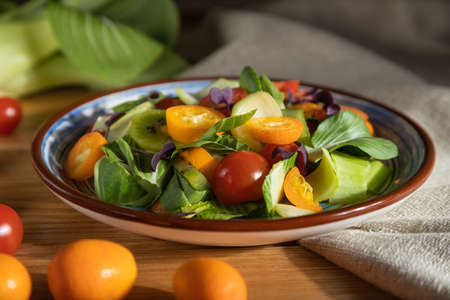 Vegetarian salad of pac choi cabbage, kiwi, tomatoes, kumquat, microgreen sprouts on a wooden background and linen textile. Hard light, contrast. Side view, close up, selective focus.