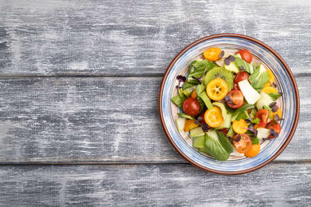 Vegetarian salad of pac choi cabbage, kiwi, tomatoes, kumquat, microgreen sprouts on gray wooden background. Top view, flat lay, copy space. Banco de Imagens