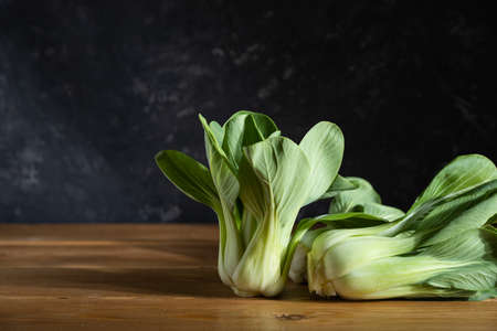 Fresh green bok choy or pac choi chinese cabbage on a gray wooden background. Hard light, contrast, dark, moody. Side view, copy space, selective focus. Banco de Imagens