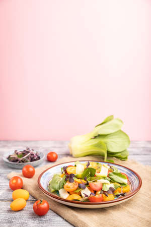 Vegetarian salad of pac choi cabbage, kiwi, tomatoes, kumquat, microgreen sprouts on gray and pink background and linen textile. Side view, close up, selective focus, copy space.