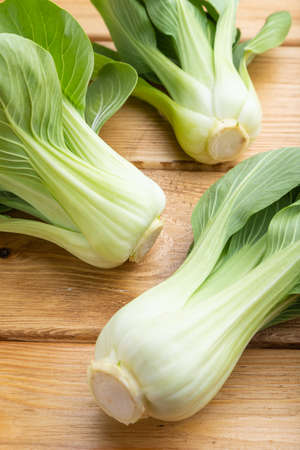 Fresh green bok choy or pac choi chinese cabbage on a brown wooden background. Side view, close up. Banco de Imagens