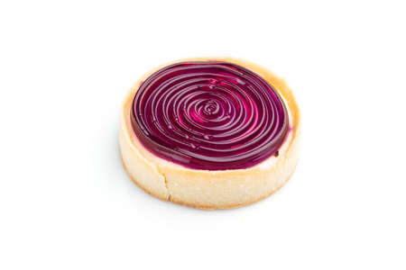 Single sweet tartlet with jelly and milk cream isolated on white background. Side view, close up.