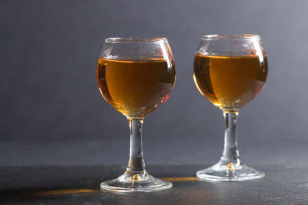 Glass of amber whiskey on a black stone slate board on black background. Side view, close up, selective focus. Stock Photo