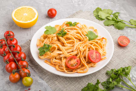 Semolina pasta with tomato pesto sauce, orange and herbs on a white ceramic plate on a gray concrete background. Side view, close up.