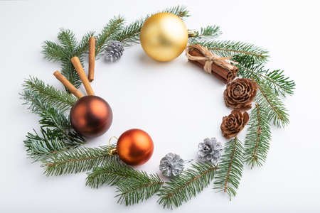 Christmas or New Year wreath composition. Decorations, balls, cones, fir and spruce branches, on white background. Side view, copy space.