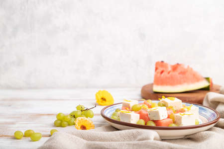 Vegetarian salad with watermelon, feta cheese, and grapes on blue ceramic plate on white wooden background and linen textile. Side view, copy space, selective focus.