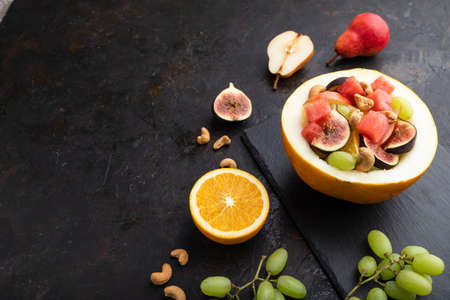 Vegetarian fruit salad of watermelon, grapes, figs, pear, orange, cashew on slate board on a black concrete background. Side view, copy space.