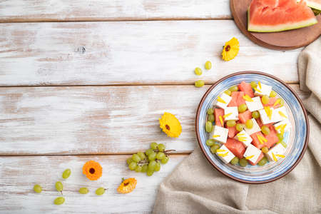 Vegetarian salad with watermelon, feta cheese, and grapes on blue ceramic plate on white wooden background and linen textile. top view, copy space, flat lay.