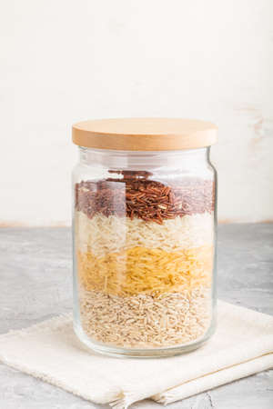 glass jar with different kinds of rice poured in layers on a gray and white background. side view, close up. Healthy food concept.