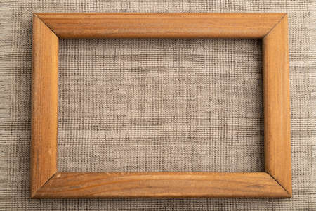 Wooden frame on smooth brown linen tissue. Top view, flat lay, natural textile background and texture.