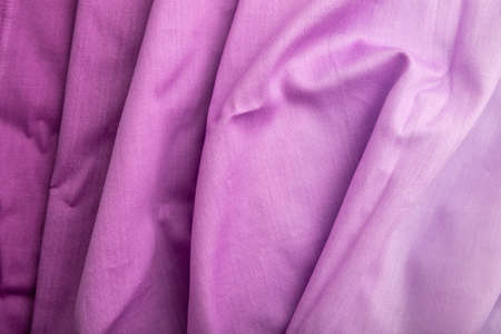 Fragment of cotton purple tissue. Top view, natural textile background and texture. wave concept, abstract.