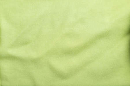 Fragment of smooth green linen tissue. Top view, flat lay, natural textile background and texture.