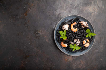 Black cuttlefish ink pasta with shrimps or prawns and small octopuses on black concrete background. Top view, flat lay, copy space.