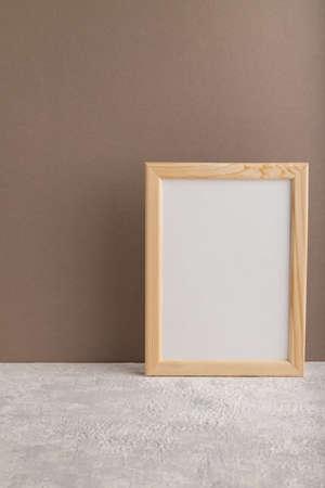 White wooden frame mockup on beige paper background. Blank, vertical orientation, still life, copy space.