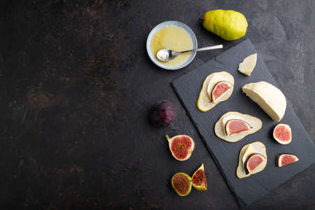 Summer appetizer with pear, cottage cheese, figs and honey on slate board on a black concrete background. Top view, flat lay, copy space.