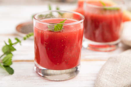 Watermelon juice with chia seeds and mint in glass on a white wooden background with linen textile. Healthy drink concept. Side view, close up, selective focus. Banque d'images