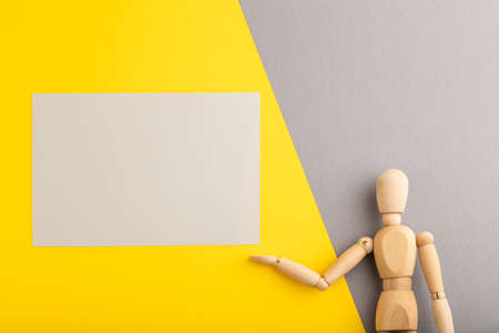 Wooden mannequin holding gray blank poster on gray and yellow pastel background. copy space, isolated, presentation concept, trendy colors.