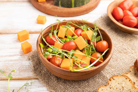 Vegetarian vegetable salad of tomatoes, pumpkin, microgreen pea sprouts on white wooden background and linen textile. Side view, close up.
