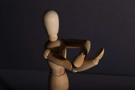 Wooden mannequin shows obscene gesture fuck off with hands on gray background. protest, riot, agression, contempt concept. copy space, hard light.