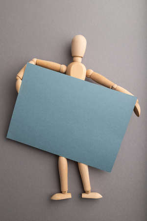 Wooden mannequin holding blue blank poster on gray pastel background. copy space, isolated, presentation concept.