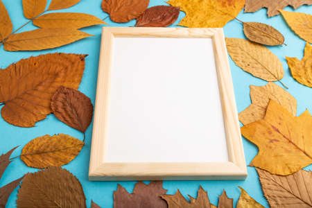 Composition with yellow and brown autumn leaves and wooden frame mockup on blue pastel background. Blank, side view, still life, copy space.