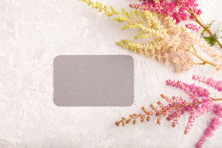 Gray paper business card mockup with purple astilbe flowers on gray concrete background. Blank, top view, copy space, still life. spring concept.