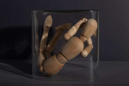 Wooden mannequin locked in a glass cube on gray background. captivity, break rules, loneliness, depression disorder concept. close up. Zdjęcie Seryjne