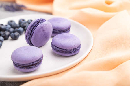 Purple macarons or macaroons cakes with blueberries on white ceramic plate on a gray concrete background and orange textile. Side view, close up, selective focus.