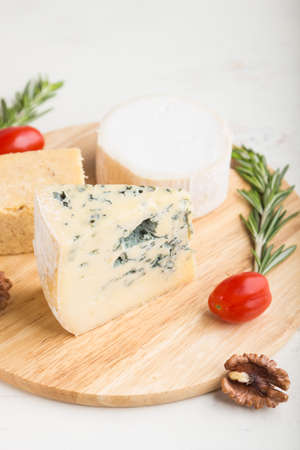 Blue cheese and various types of cheese with rosemary and tomatoes on wooden board on a white wooden background. Side view, close up, selective focus. Zdjęcie Seryjne