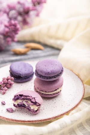 Purple macarons or macaroons cakes with cup of coffee on a gray wooden background and white linen textile. Side view, close up, selective focus. Zdjęcie Seryjne