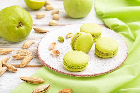 Green macarons or macaroons cakes with cup of coffee on a white wooden background and green linen textile. Side view, close up.