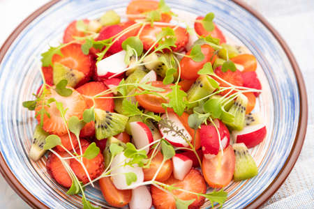 Vegetarian fruits and vegetables salad of strawberry, kiwi, tomatoes, microgreen sprouts on white concrete background and linen textile. Side view, close up, selective focus.