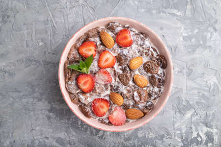 Chocolate cornflakes with milk, strawberry and almonds in ceramic bowl on gray concrete background. Top view, flat lay, close up.