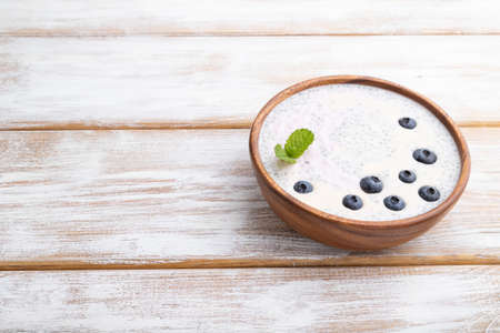 Yogurt with blueberry in wooden bowl on white wooden background. Side view, copy space, close up. Zdjęcie Seryjne