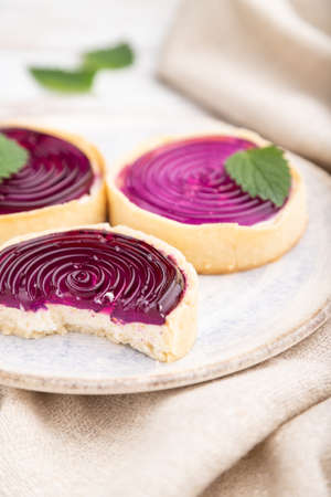 Sweet tartlets with jelly and milk cream with cup of coffee on a white wooden background and linen textile. Side view, close up, selective focus.