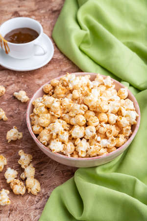 Popcorn with caramel in ceramic bowl on brown concrete background and green textile. Side view, close up.