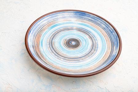 Empty blue ceramic plate on white concrete background. Side view, close up. Zdjęcie Seryjne