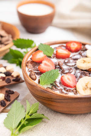 Chocolate cornflakes with milk and strawberry in wooden bowl on white wooden background and linen textile. Side view, close up, selective focus. Zdjęcie Seryjne
