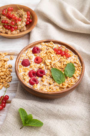 Wheat flakes porridge with milk, raspberry and currant in wooden bowl on white wooden background and linen textile. Side view, close up.