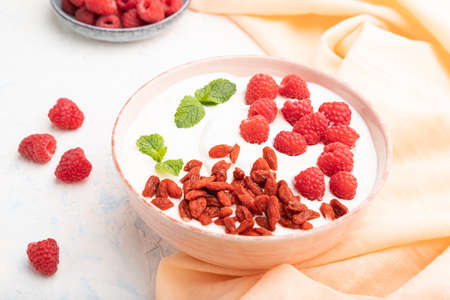Yogurt with raspberry and goji berries in ceramic bowl on white concrete background and orange linen textile. Side view, close up.