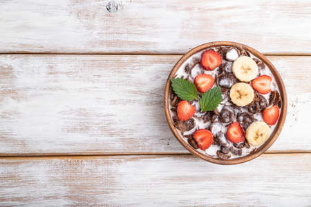 Chocolate cornflakes with milk and strawberry in wooden bowl on white wooden background. Top view, flat lay, copy space.