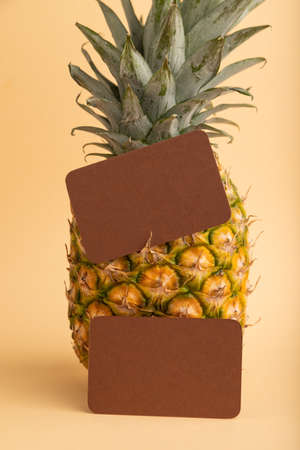 Brown paper business card with ripe pineapple on orange pastel background. Side view, copy space. Tropical, healthy food, vacation, holidays concept.