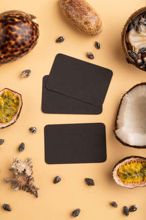 Brown paper business card with coconut, passion fruit, seashells, on orange pastel background. Top view, flat lay, copy space. Tropical, healthy food, vacation, holidays concept. Zdjęcie Seryjne