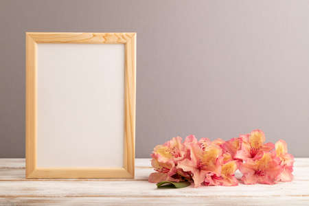 Wooden frame with pink azalea flowers on gray pastel background. side view, copy space, mockup, template, spring, summer minimalism concept.