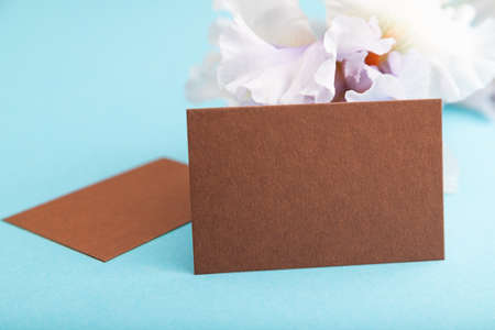 Brown business card with lilac iris flowers on blue pastel background. side view, copy space, still life. Breakfast, morning, spring concept. Zdjęcie Seryjne