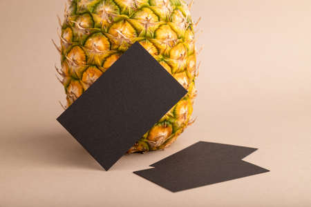 Black paper business card with ripe pineapple on orange pastel background. Side view, copy space. Tropical, healthy food, vacation, holidays concept.